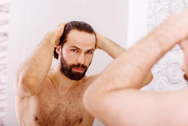 Hübscher junger mann, der sein haar mit der hand berührt und bei der stellung vor dem spiegel lächelt