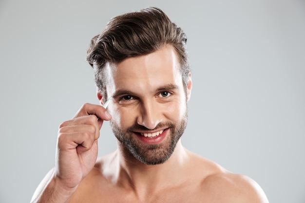 Hübscher junger mann, der seine augenbrauen mit einer pinzette zupft