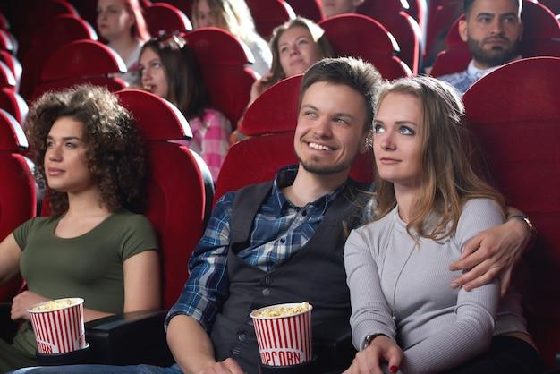 Hübscher junger mann, der seine schöne freundin umarmt, während sie einen film zusammen im kino leute lebensstil romantik dating beziehungen unterhaltung kuscheln umarmung romantisch ansehen.