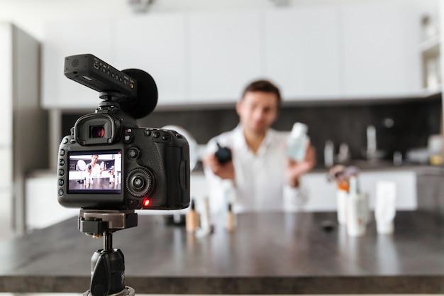 Hübscher junger mann, der seine videoblogepisode filmt