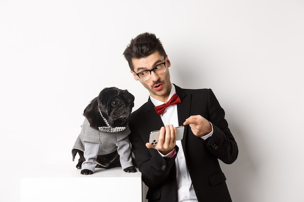 Hübscher junger mann, der seinem hund etwas auf dem handy zeigt. besitzer, die online mit haustier einkaufen, in kostümen auf weißem hintergrund stehen