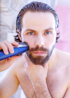 Hübscher junger mann, der seinen bart mit elektrorasierer rasiert