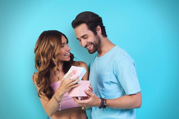 Hübscher junger mann, der seiner freundin eine geschenkbox gibt, während er vor blauem hintergrund steht