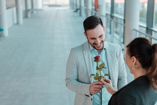 Hübscher junger mann, der seiner freundin eine rose gibt. überraschungsbesuch bei der arbeit.