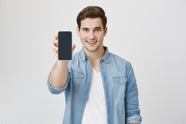 Hübscher junger mann, der smartphone-anwendung zeigt