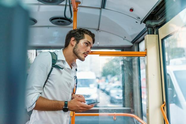Hübscher junger mann, der smartphone im bus verwendet