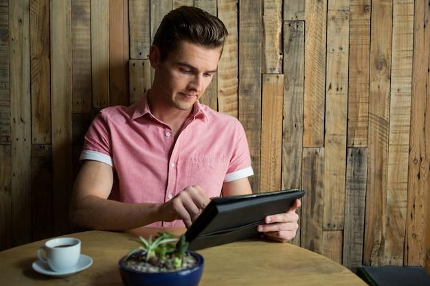 Hübscher junger mann, der tablet-computer am tisch im kaffeehaus verwendet