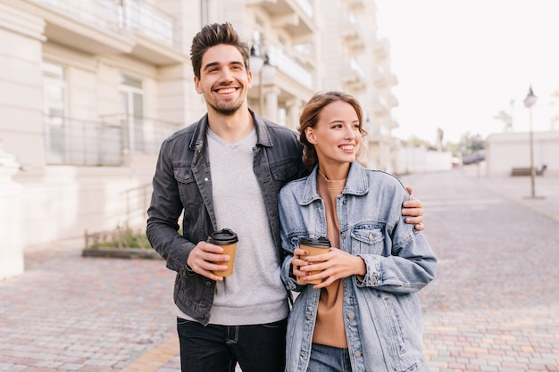 Hübscher junger mann, der tasse kaffee hält und freundin umarmt. lächelndes paar, das datum im freien genießt.