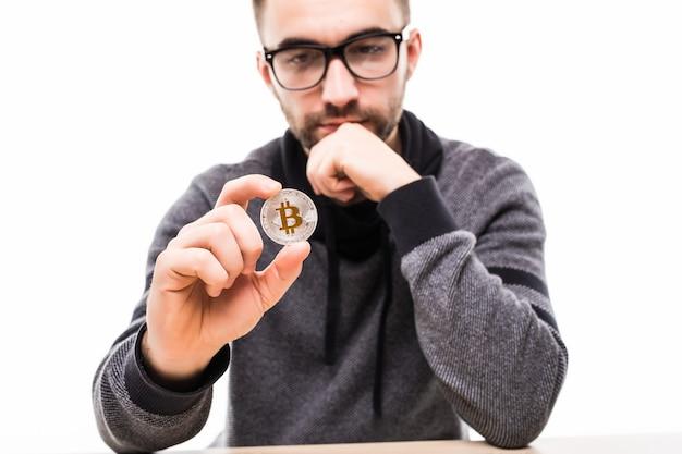 Hübscher junger mann, der über bitcoin lokalisiert auf weiß lokalisiert
