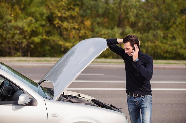 Hübscher junger mann, der um hilfe mit seinem auto ruft, das am straßenrand kaputt ist