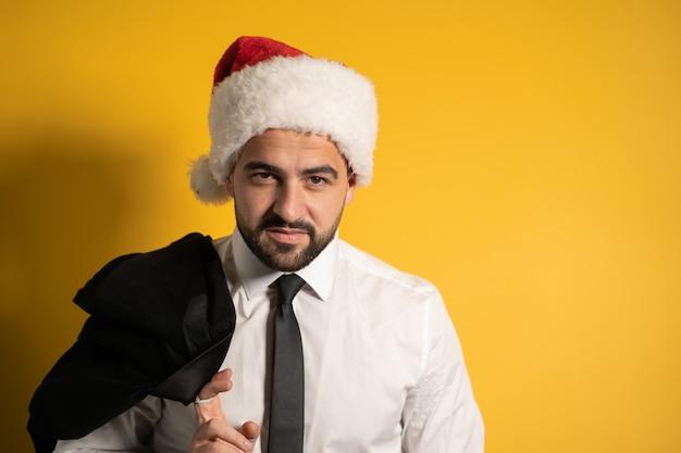 Hübscher junger mann, der weihnachtsmütze während der weihnachtszeit trägt und bereit ist, den mitarbeitern zu gratulieren