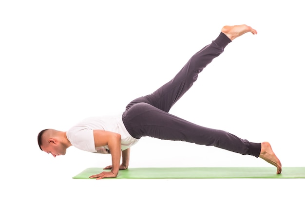 Hübscher junger mann, der yoga-pose lokalisiert auf einem weißen hintergrund tut