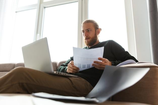 Hübscher junger mann, der zu hause arbeitet, sitzt auf einer couch unter verwendung des laptop-computers