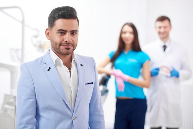 Hübscher junger mann, der zur kamera lächelt, die an der zahnklinik seinen zahnarzt und die krankenschwester aufstellt, die copyspace-professionalität stehen, vertrauen glücksdienstzahnmedizin mündliches lächeln.