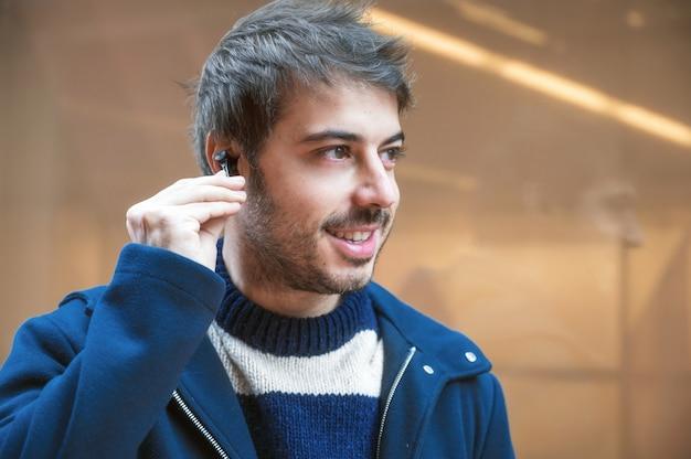 Hübscher junger mann, drahtlose kopfhörer beim gehen anziehend, städtischer stadthintergrund.