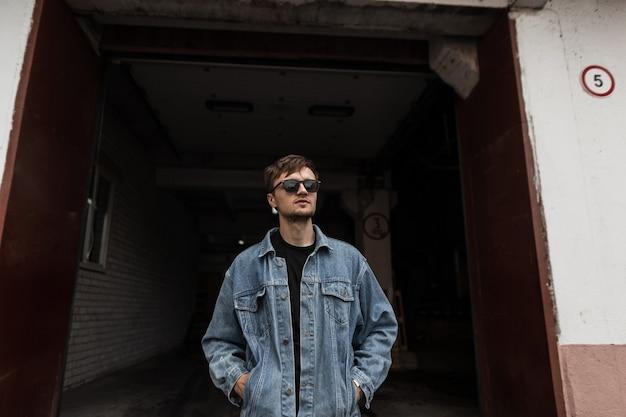 Hübscher junger mann hipster in der schwarzen sonnenbrille in einer blauen jeans stilvolle jacke mit einer trendigen frisur mit bart steht in der nähe eines gebäudes in der stadt. attraktiver cooler typ. street youth herrenmode.