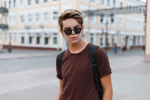 Hübscher junger mann hipster in sonnenbrille in einem braunen trendigen t-shirt mit einer stilvollen frisur geht durch die stadt an einem warmen sommertag auf dem hintergrund von vintage-gebäuden