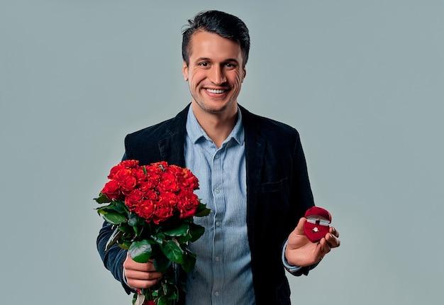 Hübscher junger mann im anzug posiert auf grau mit ring und roten rosen in den händen, schaut in die kamera und lächelt.
