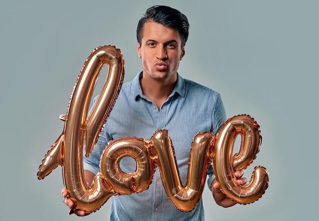 Hübscher junger mann im blauen hemd steht mit luftballon beschriftet liebe in den händen bläst einen kuss auf grau.