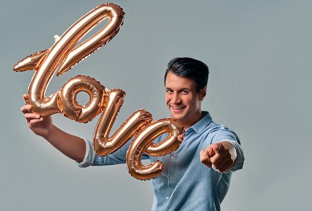 Hübscher junger mann im blauen hemd steht mit luftballon beschriftet liebe in der hand und zeigt einen finger auf sie auf grau.