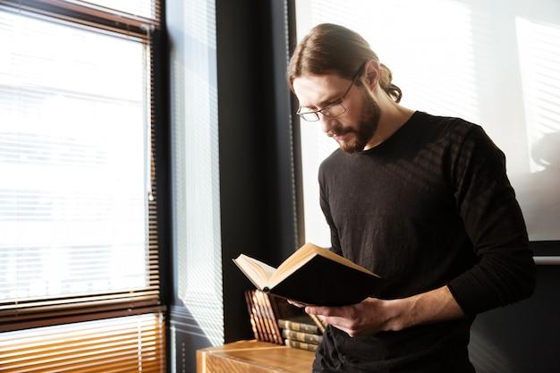 Hübscher junger mann im büro, das beim lesen des buches arbeitet.
