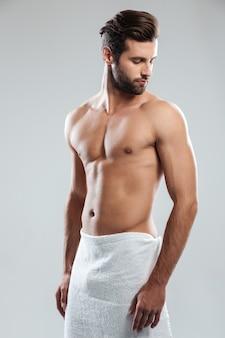 Hübscher junger mann im handtuch gekleidet