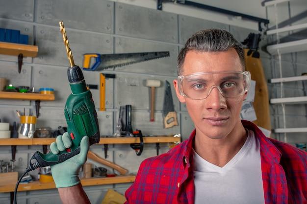 Hübscher junger mann im karierten hemd, sicherheitsbrille zum schutz, handschuhe, die mit bohrmaschine bohren, arbeiten in der tischlerei