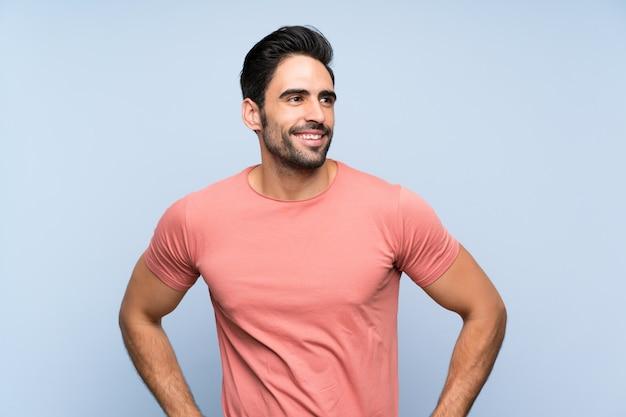 Hübscher junger mann im rosa hemd über lokalisierter blauer aufstellung mit den armen an der hüfte und am lächeln
