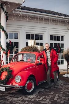 Hübscher junger mann im roten mantel, der durch ein rotes altes auto nahe einem haus steht
