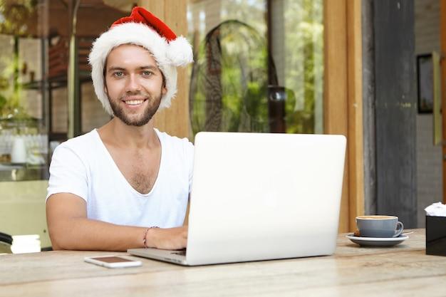 Hübscher junger mann im roten weihnachtsmannhut, der glücklich kamera betrachtet, während laptop-computer für fernarbeit verwendet, weihnachtsferien im tropischen land verbringend