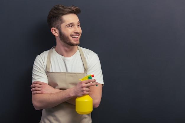Hübscher junger mann im schutzblech hält einen sprüher.