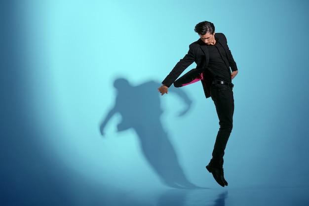 Hübscher junger mann im schwarzen stilvollen anzug, springend, lokalisiert auf blauem hintergrund. horizontale ansicht.