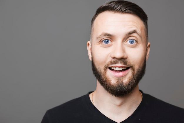 Hübscher junger mann im schwarzen t-shirt, das kamera mit aufgeregtem gesichtsausdruck beim stehen auf grauem hintergrund betrachtet