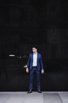 Hübscher junger mann im vollen anzug und in den schuhen, die gegen wand aufwerfen