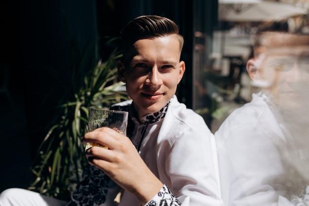 Hübscher junger mann im weißen anzug mit stickerei sitzt auf einem fensterbrett vor hellem fenster