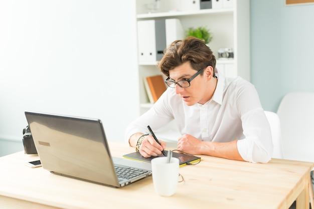 Hübscher junger mann im weißen hemd unter verwendung der grafiktafel am holztisch
