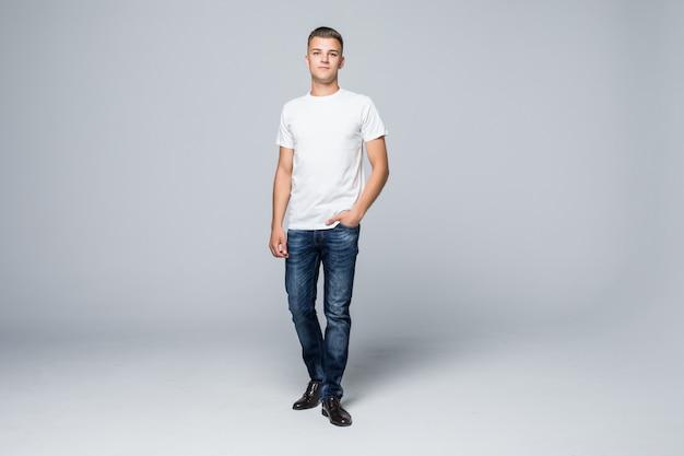 Hübscher junger mann im weißen t-shirt der lässigen artkleidung und in den blauen jeans auf weiß