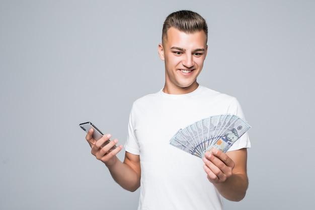 Hübscher junger mann im weißen t-shirt hält viele dollarnoten in seinen händen, die auf weiß isoliert werden