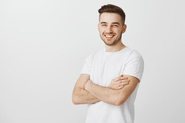 Hübscher junger mann im weißen t-shirt, verschränkte brust und lächelnd erfreut
