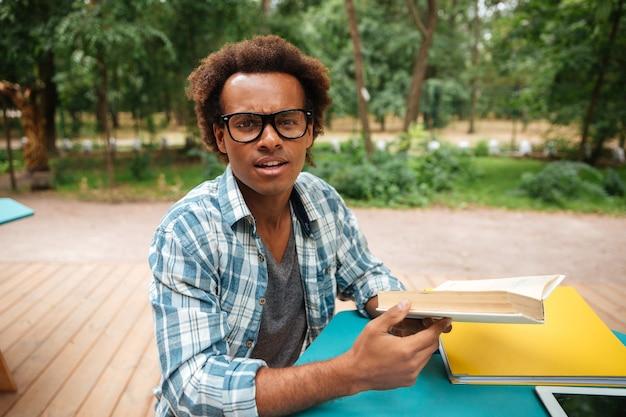 Hübscher junger mann in den gläsern, die im straßencafé lesen und lernen