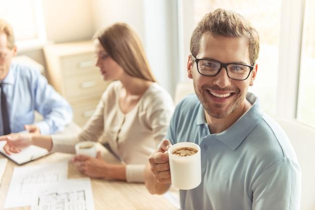 Hübscher junger mann in den gläsern hält tasse kaffee.