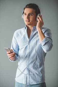 Hübscher junger mann in den kopfhörern hört musik