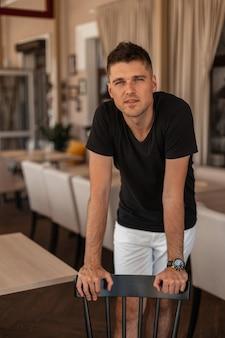 Hübscher junger mann in den trendigen weißen shorts in einem schwarzen stilvollen t-shirt mit einer modischen frisur steht in der nähe eines hölzernen vintage-stuhls in einem café.