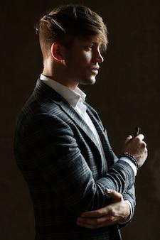 Hübscher junger mann in der grauen klage steht mit einer zigarre