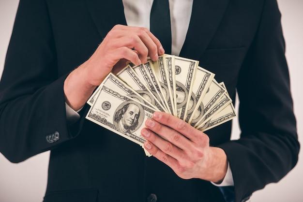 Hübscher junger mann in der klage, die geld hält