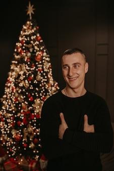 Hübscher junger mann in der schwarzen kleidung nahe einem weihnachtsbaum in girlanden