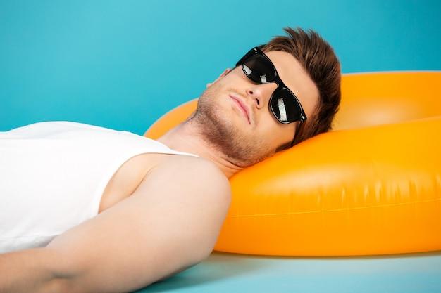 Hübscher junger mann in der sonnenbrille, die auf aufblasbarem ring entspannt