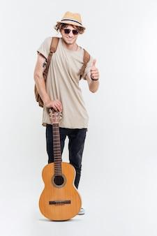 Hübscher junger mann in der sonnenbrille, die die gitarre hält und daumen oben auf einem weißen hintergrund zeigt