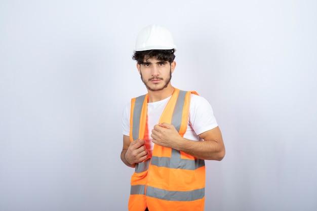 Hübscher junger mann in der uniform, die über weißer wand steht. hochwertiges foto