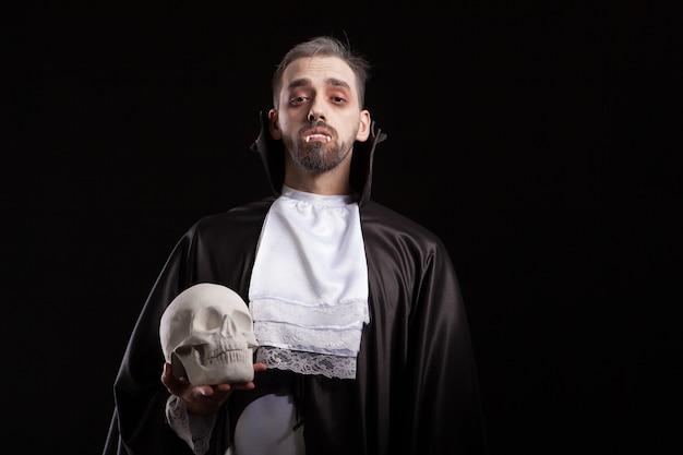 Hübscher junger mann in dracula-kostüm für halloween, der einen schädel hält und in die kamera schaut. gespenstischer mann im dracula-kostüm.
